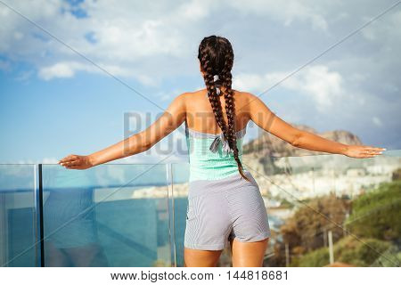 Young beautiful woman overlooking Mediterranean Sea on the blue sky
