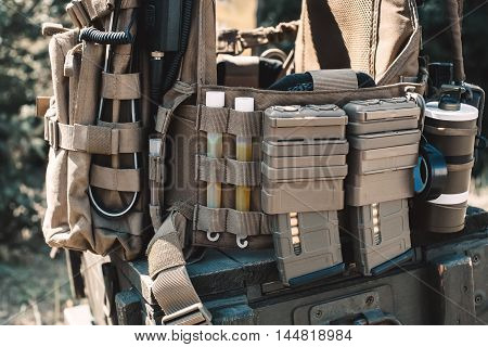 Army vest with a walkie-talkie charged collars stun grenades luminous sticks standing on a wooden box of ammunition.