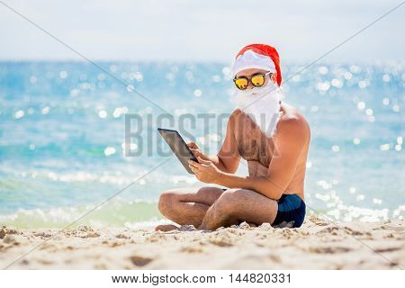 Santa Claus on the beach with a tablet in hands. Christmas holidays technology and people concept - man in costume of santa claus with tablet pc computer over tropical beach background