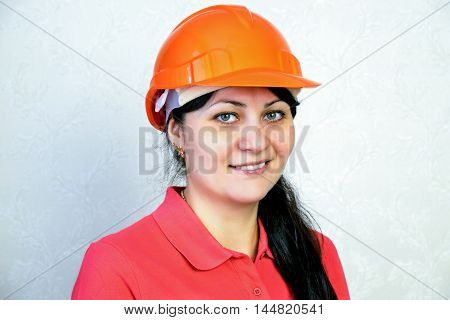 Girl the builder in a helmet. Close portrait of a smile