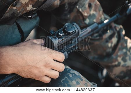 A soldier adjusts optical sight on a rifle.