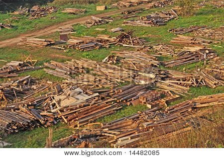 Piles Of Wooden Garbage On Green Grass
