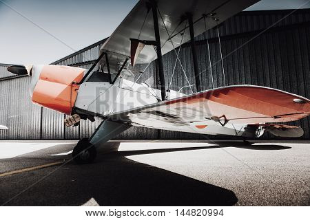 Old vintage plane parked at the aerodrome. Wings view.