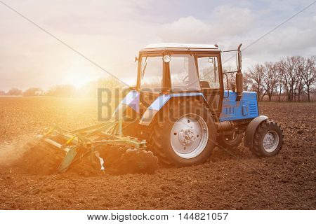 In the earlyspring morningbecause of the wood the bright sun ascends.The tractor goes and pulls a plowplowing a field before landing of crops.On the earth dry stalks of a last year's sunflower lie.