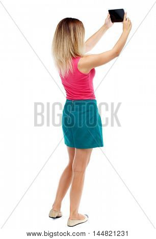 back view of standing young beautiful woman using a mobile phone. girl watching. Isolated over white background. Blonde in a red sweater and green skirt pictures of the tablet that is at the top.