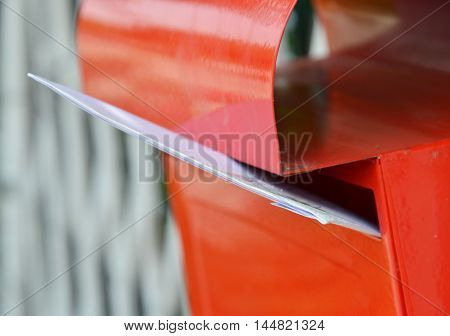 letter in red post box on home fence