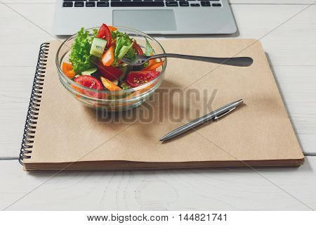 Healthy business lunch in office, vegetable salad bowl near laptop on white wooden desk and notepad with pen. Organic meal, red apple and orange juice. Snack at break time.