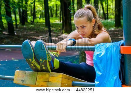 Young slim woman stretching in a training ground in a park