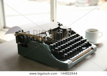 Old typewriter and cup of coffee on the table