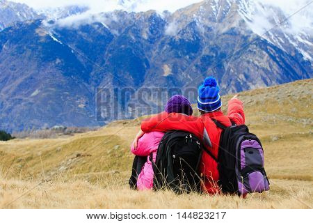 happy young tourist couple hiking in mountains