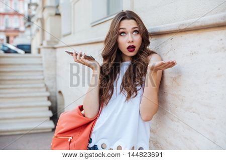 Shocked astonished beautiful young woman holding her smartphone outdoors