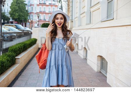 Happy surprized young woman in hat with backpack and magazines standing on the street