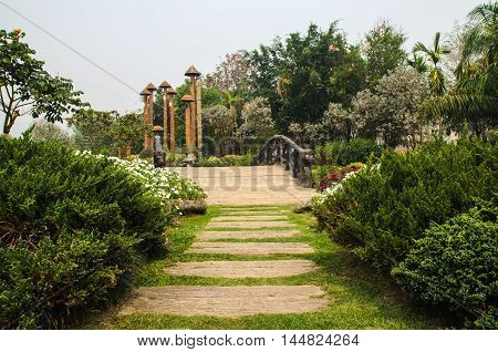 A wooden arch bridge in a garden
