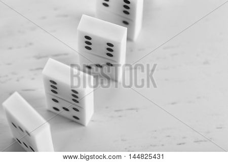 Line of dominoes standing on light wooden background