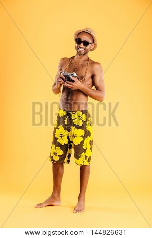 Full length portrait of a happy afro american man holding retro photo camera isolated on a orange background