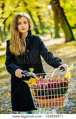 Happy active teenager riding bike in fall autumn park. Young girl relaxing with healthy lifestyle and recreation leisure activity.