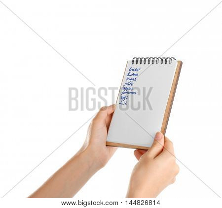 Hands holding notepad with shopping list on white background