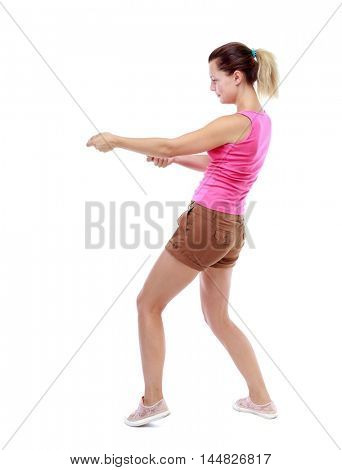 back view of standing girl pulling a rope from the top or cling to something. Isolated over white background. Sport blond in brown shorts pulls the rope.