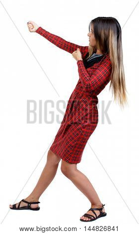 back view of standing girl pulling a rope from the top or cling to something. girl in red plaid dress stands sideways and pulling rope.