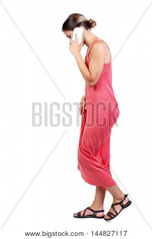 side view of a woman walking with a mobile phone. beautiful girl in motion. slender woman in a long red dress is looking at his feet and talking on white smartphone.