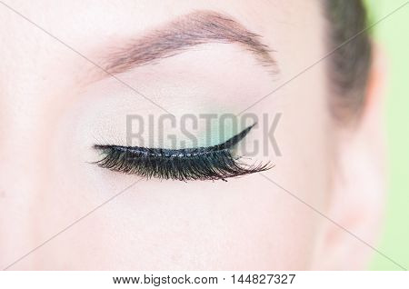Close-up of professional green eye make-up with lash extension isolated on green background