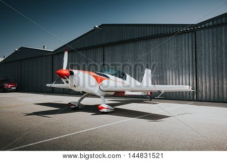 Small business plane parked in front of the hangar.