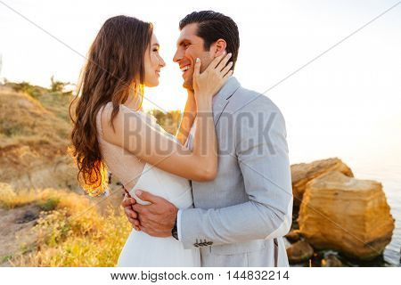 Just-married couple standing at the beach at sunset