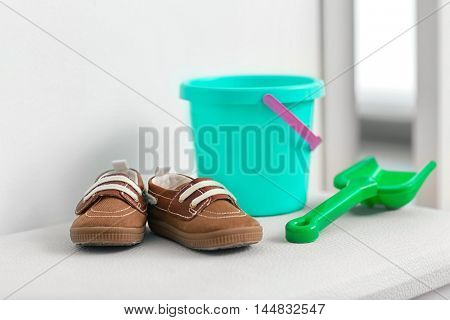 Child's shoes, bucket and shovel on table