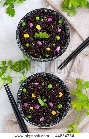 Black rice in a bowl and vegetables on marble table