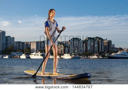 Young pretty woman on Stand Up Paddle Board. SUP. Shape of a city on background