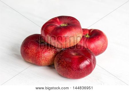 Fresh flat peach fruits on white wooden table