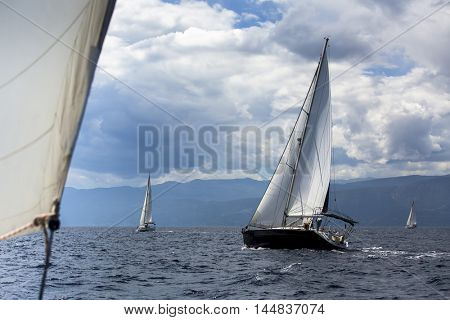 Sailing regatta in the wind through the waves at the Aegean Sea in Greece. Luxury yachts at stormy weather.
