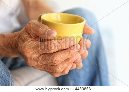 Old man holding cup of hot drink