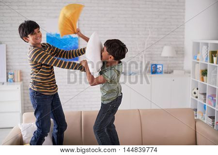 Two brothers fighting with pillows at home