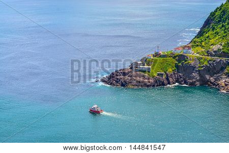 Boats motor past Fort Amherst.  Rugged coastline and Atlantic ocean. Warm summer day in August with views from atop the Historically famous Signal Hill in St. John's.