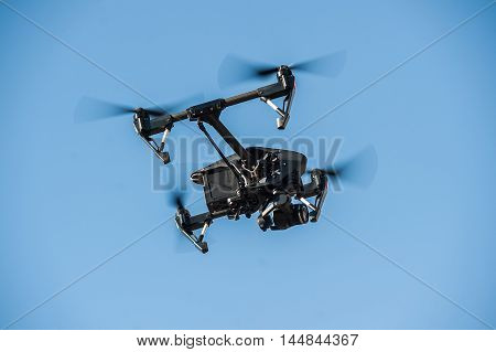 Drone-quadrocopter with camera hovers on the blue sky