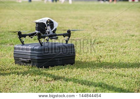 Drone with camera stands on box on background of green grass