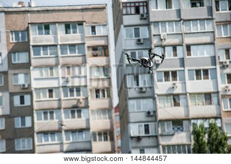 Drone with camera hovers on the background of residential building