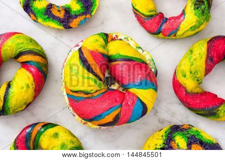 Colorful bagel with cheese and sprinkles on marble