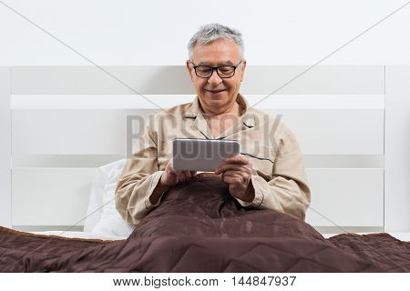 Happy senior man is lying in bed and using digital tablet.