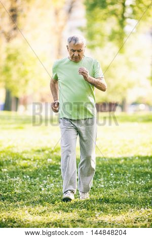 Senior man is jogging in park. Active retirement. Image is intentionally toned.
