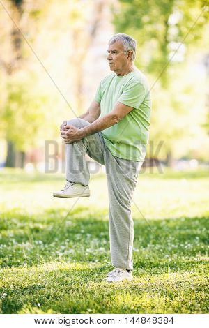 Senior man is exercising in park. Active retirement. Image is intentionally toned.