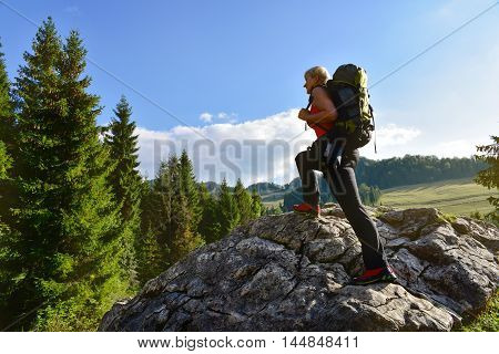 Woman hiking on the rock with backpack