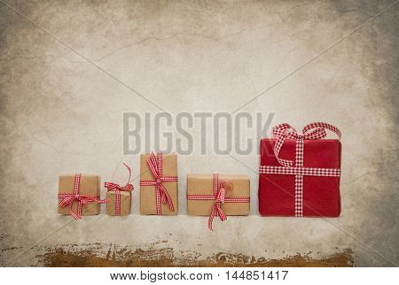 Five gift boxes wrapped with red white checked bow for christmas decoration in vintage style.