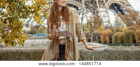 Woman On Embankment In Paris Holding Map And Looking Aside