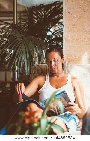 Portrait of peaceful adult woman reading illustrated magazine in arm-chair with palm plant behind.