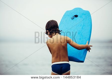 Rear view of little boy in trunks and goggles holding blue bodyboard in sea