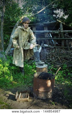 World War Two Soldier in helmet and cloak stand on stump with rubber boot as a winner