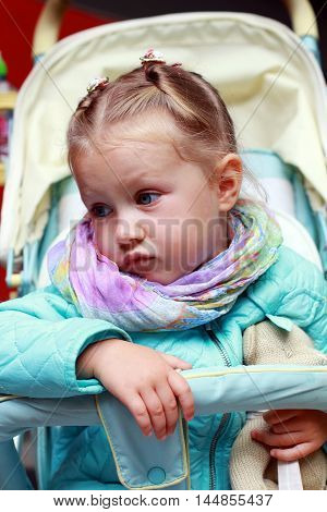 Dissatisfied little girl in a pushchair outdoor