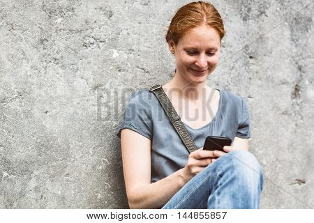 Woman With Smartphone Against A Wall